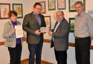 Regionalbotschafter Karl-Heinz Haseloh (2. v. rechts) übergibt die Förderurkunde an Birgitt Keil, André Gerling und Klaus Kasper vom Heimatverein Kutenhausen